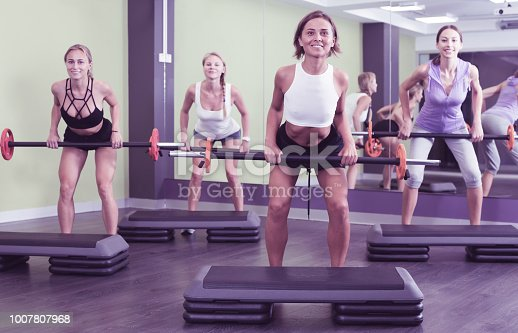 Portrait of young women exercising with barbell at health club