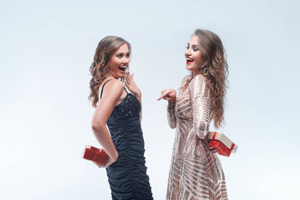 Portrait of young women friends holding gifts behind the back going to exchange them. stock photo