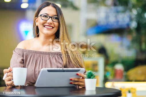 Portrait of young women in cafe with coffee cup and tablet
