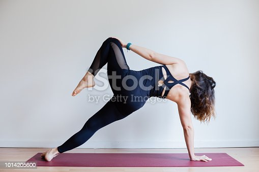 Portrait of young yogi woman practising yoga, wearing black sportswear, white studio background, side plank variation pose (selective focus)