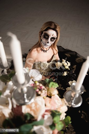 istock Portrait of zombie woman with painted skull face 1165996018