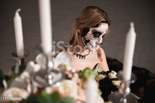 istock Portrait of zombie woman with painted skull face 1177403550