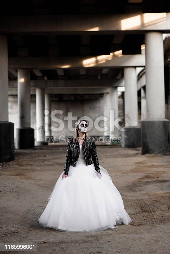 512061362istockphoto Portrait of zombie woman with painted skull face under a bridge. 1165996001