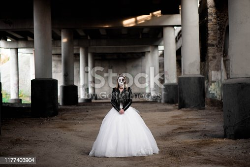 istock Portrait of zombie woman with painted skull face under a bridge. 1177403904