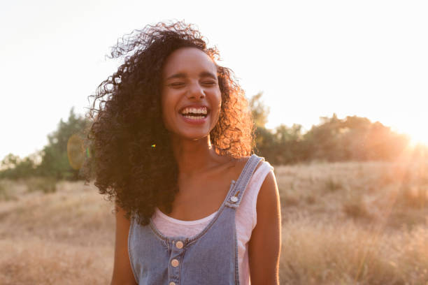portrait outdoors of a beautiful young afro american woman smiling at sunset. Yellow background. Lifestyle stock photo