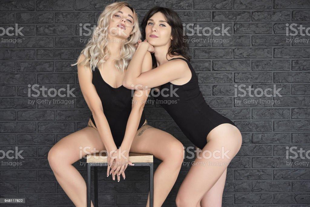 Portrait Posing Women In Black Swimsuit Sitting On A Bar Chair stock photo