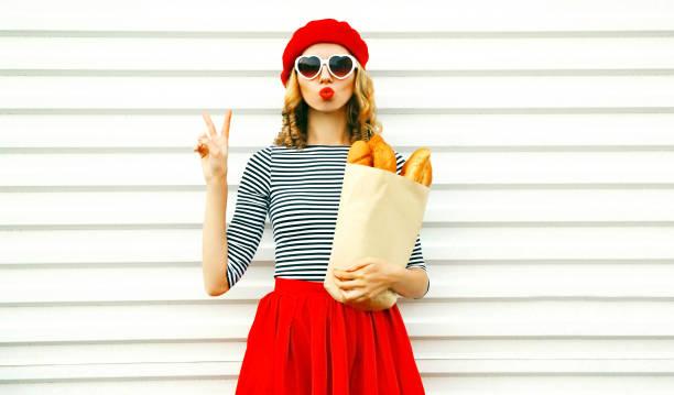 Ziemlich cooles Mädchen Porträt trägt französische rote Mütze hält Papiertüte mit lange Weißbrot Baguette auf weiße Wand Hintergrund – Foto
