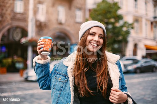 870648602istockphoto Portrait pretty girl in denim coat and knitted hat walking on street. She holds coffee to go in white gloves, smiling friendly to camera 870498960