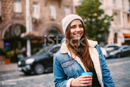 870648602istockphoto Portrait pretty girl with long hair in denim coat walking on street with coffee to go. She looks excited to camera 870498962