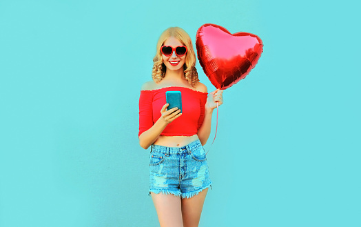 istock Portrait pretty happy smiling woman holding phone, red heart shaped air balloon on colorful blue background 1141445295
