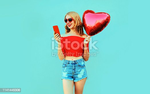 istock Portrait pretty happy smiling woman holding phone, red heart shaped air balloon on colorful blue background 1141445306