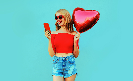 istock Portrait pretty happy smiling woman holding phone, red heart shaped air balloon on colorful blue background 1202899263