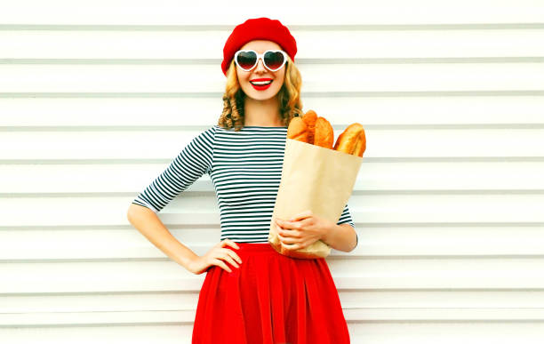 Portrait pretty smiling woman wearing red beret holding paper bag with long white bread baguette on white wall background stock photo