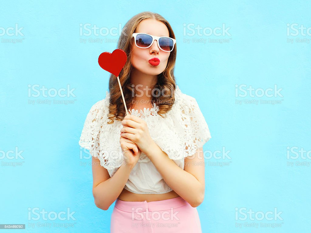 Portrait pretty woman and red lollipop over colorful blue background stock photo