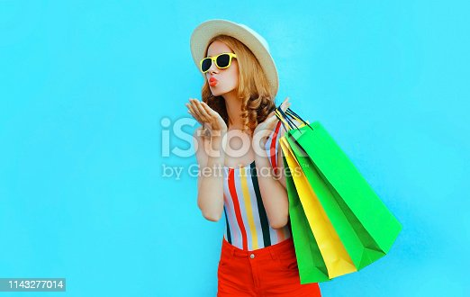 615594632 istock photo Portrait pretty woman blowing red lips sends air kiss with shopping bags in colorful t-shirt, summer round hat on blue background 1143277014