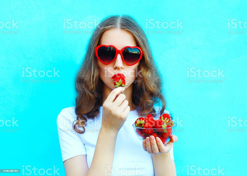 Portrait pretty woman with many strawberry over colorful blue stock photo