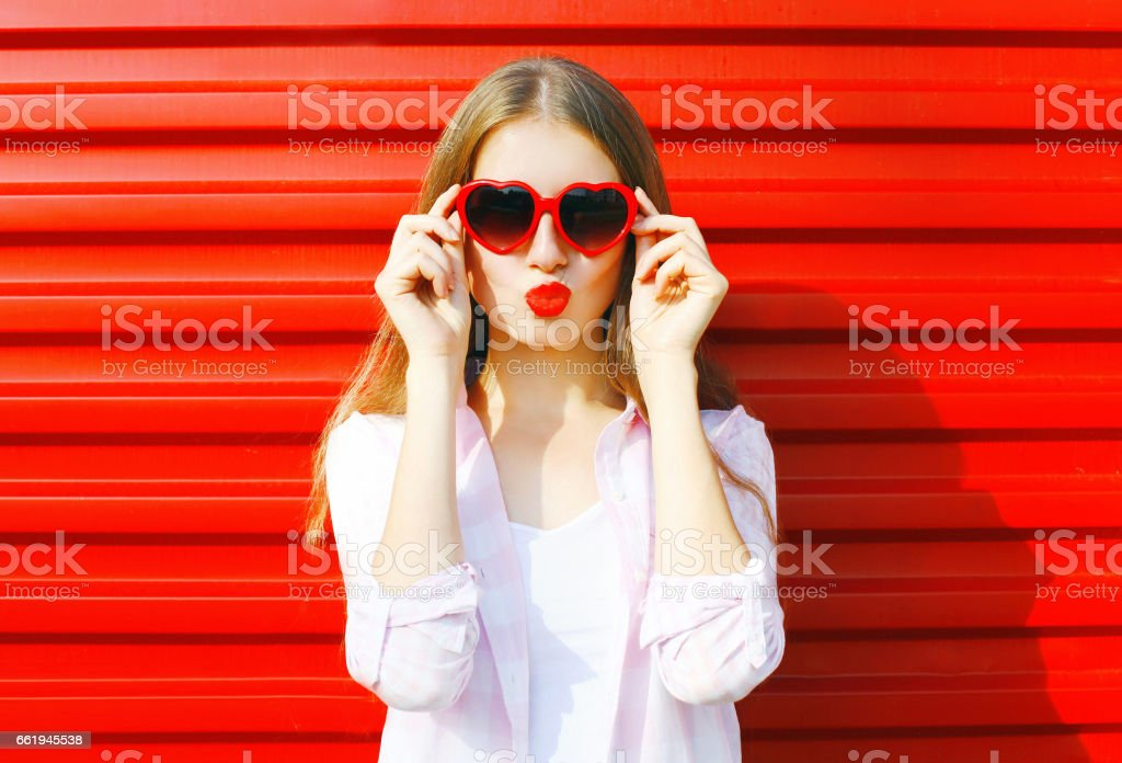Portrait pretty young woman in red heart shape sunglasses over colorful background blowing lips