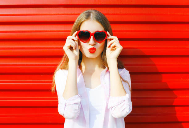 Portrait pretty young woman in red heart shape sunglasses over colorful background blowing lips bildbanksfoto