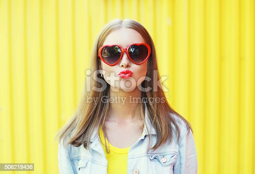 istock Portrait pretty young woman in red sunglasses blowing lips kiss 506219436