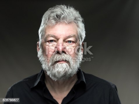 Portrait of real man, with white beard and blue eyes, looking confident straight in the camera on grey background