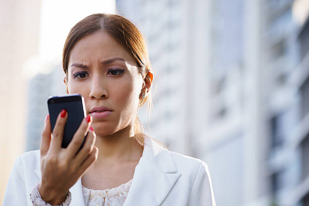 Portrait sad business woman typing sms phone street stock photo
