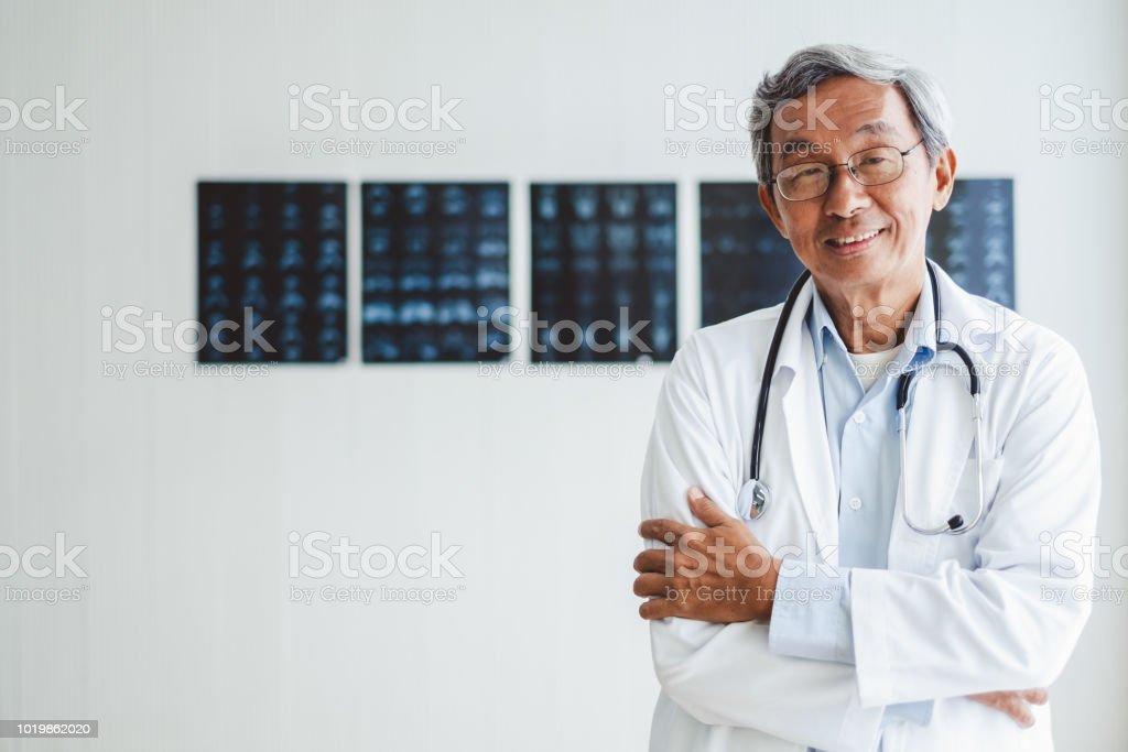 Porträtt asiatiska överläkare över radiografi bakgrund, Asiatiska medicinska begrepp - Royaltyfri Akademikeryrke Bildbanksbilder