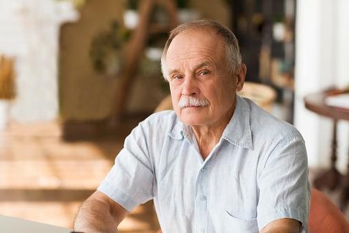portrait senior man thinking and looking at camera at home