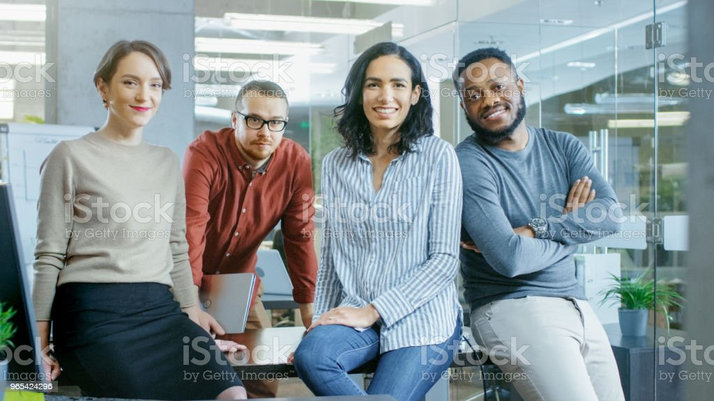 Portrait Shot of a Diverse Group of Talented Young Professionals Sitting on a Desk in the Stylish Modern Environment. Real People Sincerely Smiling on Camera. zbiór zdjęć royalty-free