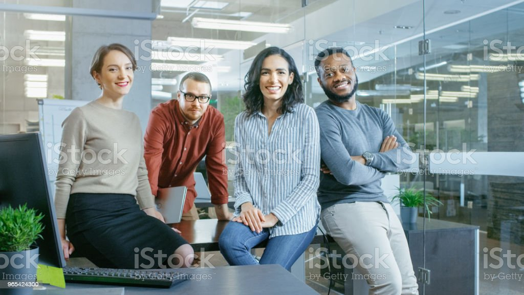 Portrait Shot of a Diverse Group of Talented Young Professionals Sitting on a Desk in the Stylish Modern Environment. Real People Sincerely Smiling on Camera. royalty-free stock photo