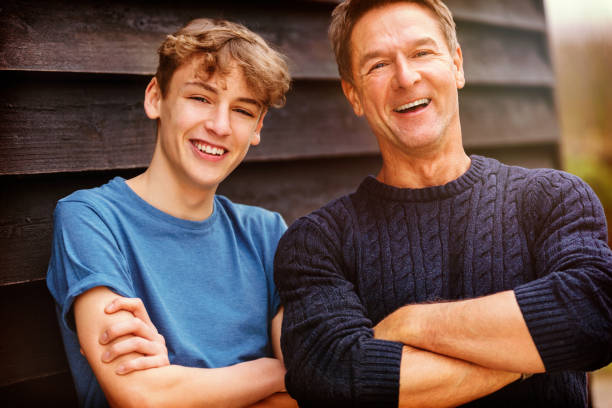 Foto de retrato de un hombre de mediana edad atractivo, exitoso y feliz hombre de mediana edad brazos masculinos doblados con su hijo adolescente fuera riendo adolescente, usando un suéter azul y camiseta - foto de stock