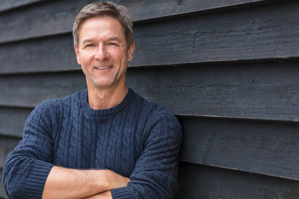 Portrait shot of an attractive, successful and happy middle aged man male arms folded outside wearing a blue sweater - foto de stock