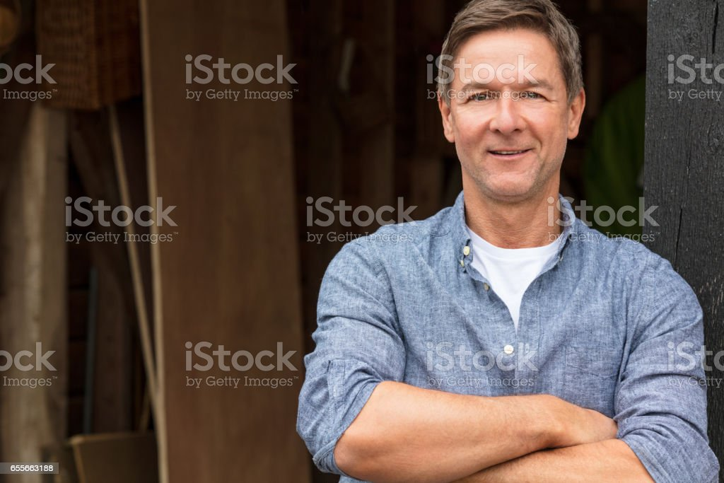 Portrait shot of an attractive, successful and happy middle aged man male arms folded outside wearing a blue shirt outside his garage or shed stock photo