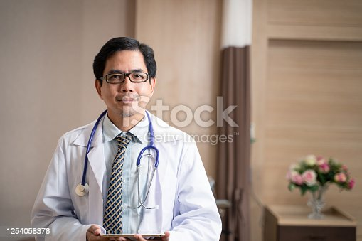 Portrait shot of male medical doctor in medic gown uniform holding tablet, looking at camera and smile in patient recovery room in hospital. Asian experience professional doctor smiling in hospital.