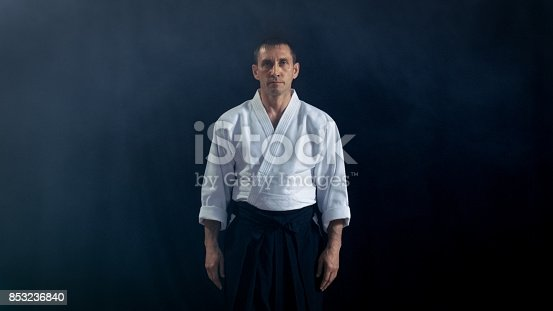 istock Portrait Shot of the Aikido Master Wearing Traditional Samurai Hakama Clothes Looking into Camera. He's in the Spotlight Darkness Surrounds Him. Shot Isolated on Black Background. 853236840