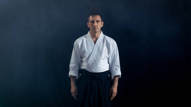 Portrait Shot of the Aikido Master Wearing Traditional Samurai Hakama Clothes Looking into Camera. He's in the Spotlight Darkness Surrounds Him. Shot Isolated on Black Background. stock photo