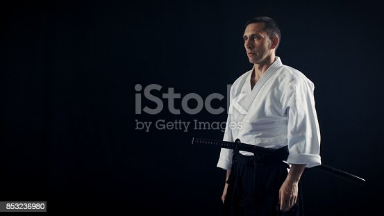 istock Portrait Shot of the Aikido Master Wearing Traditional Samurai Hakama Clothes Holds His Japanese Sword. He's in the Spotlight Darkness Surrounds Him. Shot Isolated on Black Background. 853236980