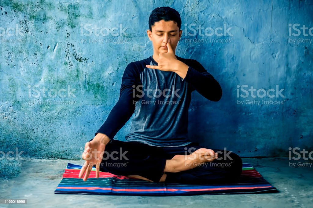 Portrait shot of the young man doing pranayama or pranayam or breath control yoga on a colorful mat with wearing black attire. Portrait shot of the young man doing pranayama or pranayam or breath control yoga on a colorful mat with wearing black attire. Adult Stock Photo