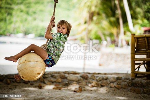 Cute small boy swinging and looking at camera on summer vacation