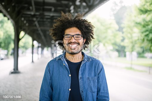 Portrait smiling african man wearing glasses. Man with curly hair standing under a city bridge and looking at camera.