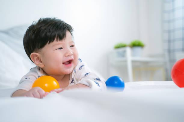 Retrato sonriente niño asiático en la cama. Niño recién nacido relajante. Guardería para niños pequeños - foto de stock