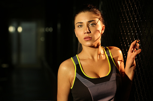 629605142 istock photo Portrait smiling fitness girl near fence of grid in gym 502814010