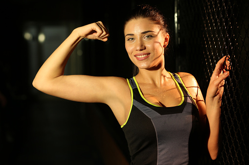 629605142 istock photo Portrait smiling fitness girl near fence of grid in gym 502814018