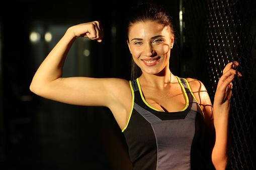 629605142 istock photo Portrait smiling fitness girl near fence of grid in gym 502814036