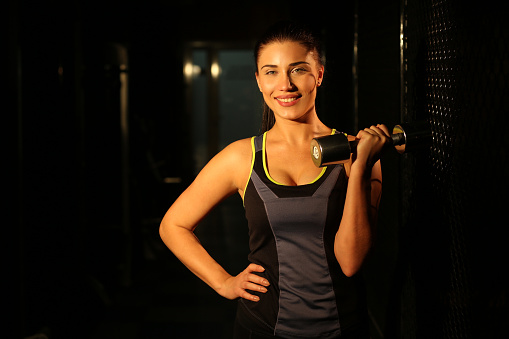 629605142 istock photo Portrait smiling fitness girl with dumbbells in gym 502814162