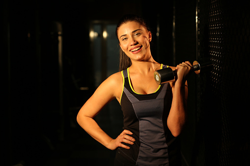 629605142 istock photo Portrait smiling fitness girl with dumbbells in gym 502814180