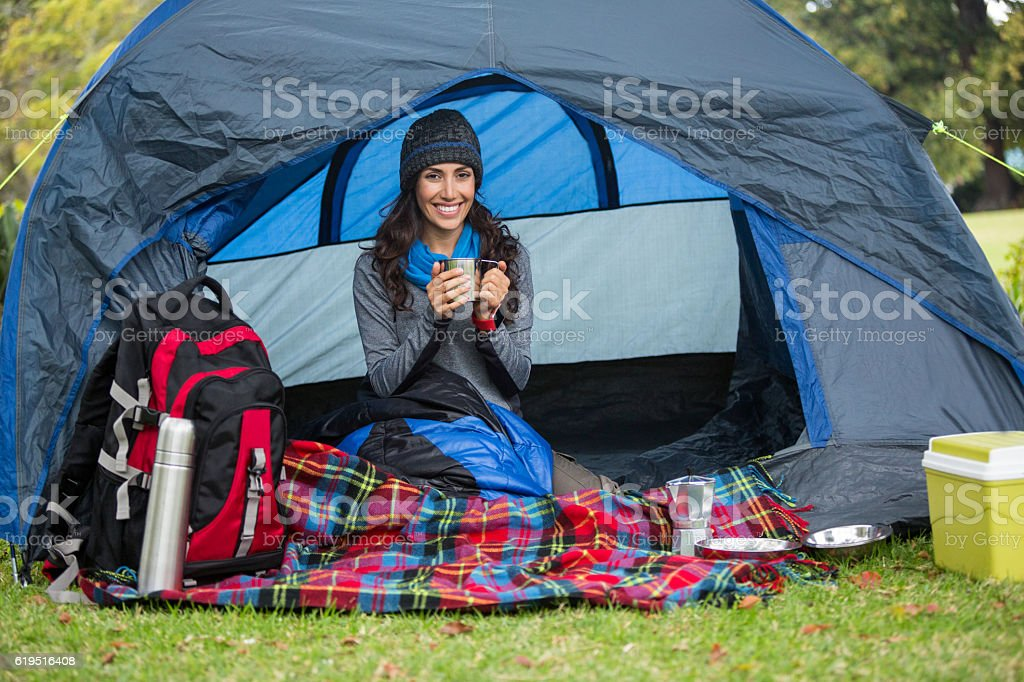 Portrait smiling hiker having  cup of coffee in tent stock photo