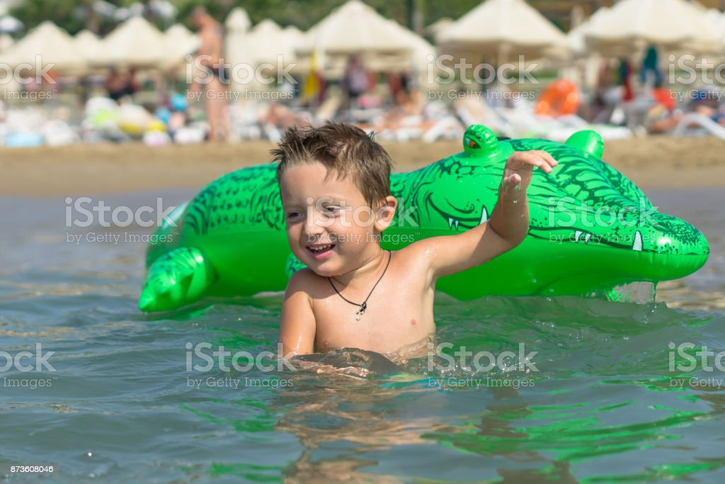 Portrait smiling little baby boy playing in the sea, ocean. Positive human emotions, feelings, joy. Funny cute child making vacations and enjoying summer. stock photo