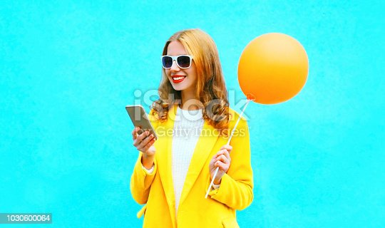 istock Portrait smiling woman using smartphone holds an air balloon on colorful blue background 1030600064