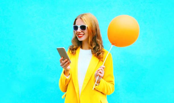 Porträt lächelnde Frau mit Smartphone hält einen Luftballon auf bunten blauen Hintergrund – Foto