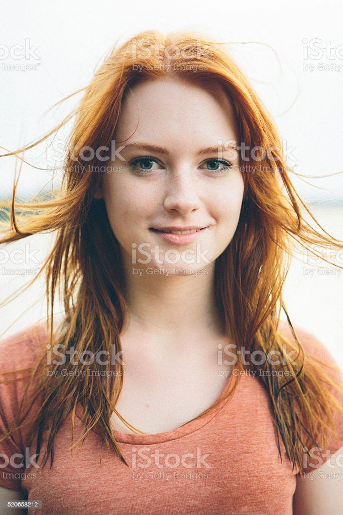 portrait smiling young redhead woman on nature background stock photo